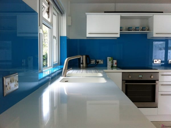 Kính ốp tường bếp màu xanh dương kết hợp bàn đá và tủ bếp trắng tạo không gian sống hiện đại