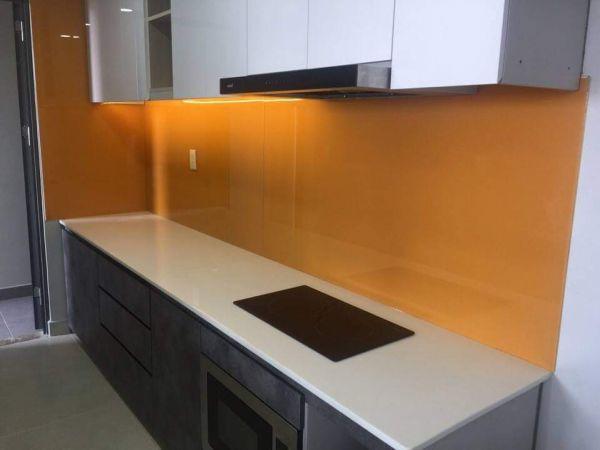 Kính sơn màu ốp bếp màu cam kết hợp tủ bếp màu trắng, bàn đá trắng