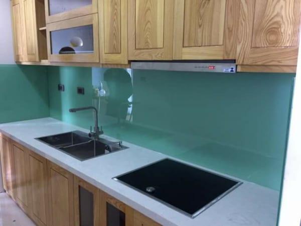 Kính ốp tường bếp màu xanh ngọc kết hợp tủ gỗ và bàn đá màu trắng