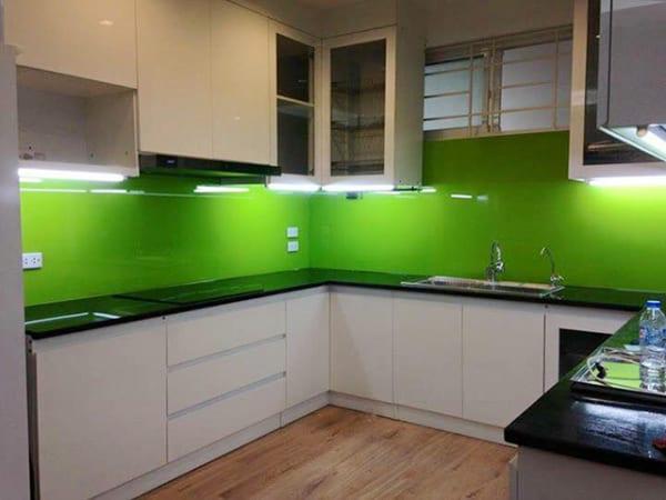 Kính ốp bếp màu xanh non kết hợp tủ bếp màu trắng, bàn đá đen