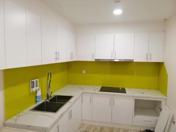 Kính ốp bếp màu vàng kết hợp bàn đá và tủ bếp màu trắng